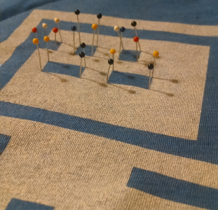 Straight pins stuck through the shirt at the intersections of each block representing the cursor text on the shirt design