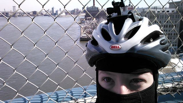 The author wearing a black balaclava under a helmet, standing before a view of the East River from the Manhattan Bridge.