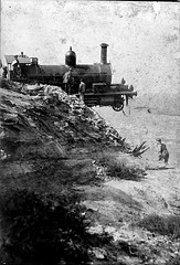 A locomotive with its nose off the edge of a cliff.